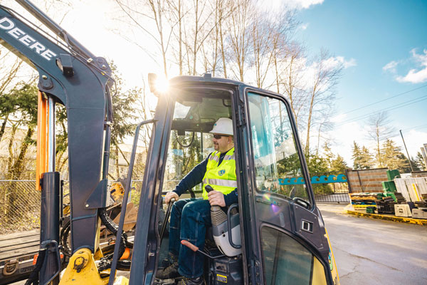 Man controlling a backhoe in a parking lot with trees behind